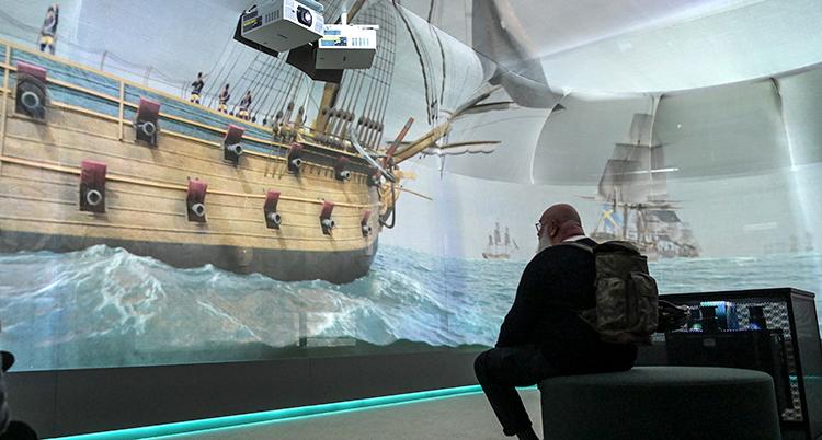En man sitter och tittar på en vägg med ett stort skepp.