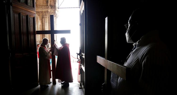 Inne i en katolsk kyrka. Det är mörkt. Några präster syns.