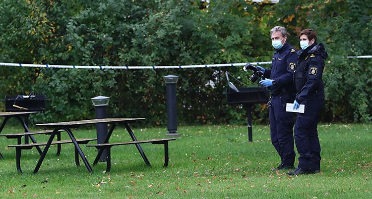 Två poliser står på en gräsmatta. En av dem har en kamera.