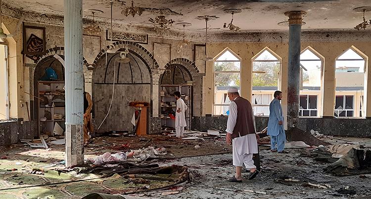 Några människor går runt i en moské och tittar på allt som blivit förstört. Det ligger massa skräp och bråte på golvet.