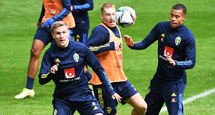 Från en träning i fotboll. Tre spelare kämpar om bollen.