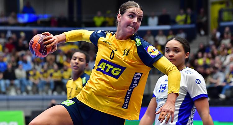 Från en match i handboll. En svensk spelare hoppar för att skjuta. Hon har bollen i handen.