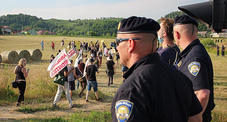 Människor protesterar på ett stort fält. Poliser tittar på.
