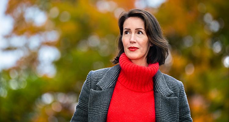Hon är utomhus. Hon har en röd tröja och grå kavaj. I bakgrunden syns träd med höstfärger.