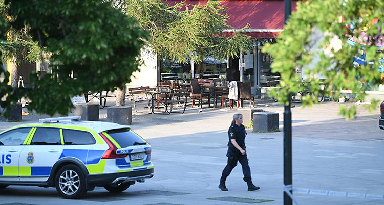 Ett torg i Sätra. En polisbil står där och en kvinnlig polis går över torget. Längre bort syns en restaurang.