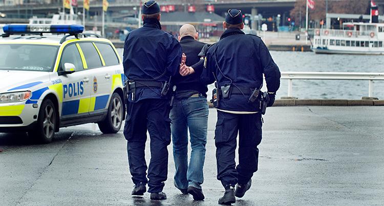 Två poliser håller fast en man och går mot en polisbil.