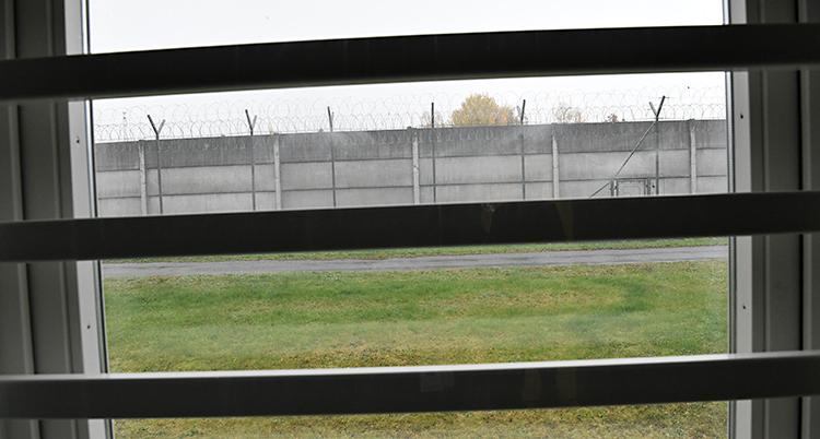 Bilden är tagen inifrån ett fängelse. Det är galler för fönstret. Längre bort syns en hög mur med taggtråd.