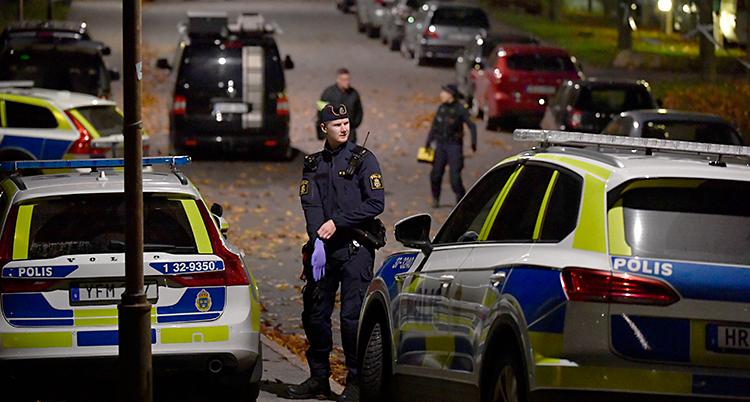 Flera poliser och flera polisbilar står på en gata.