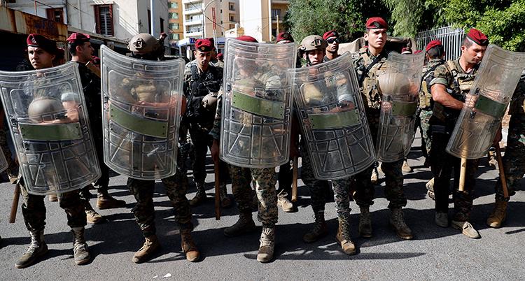Militärer står intill varandra på gatan. De har uniformer och sköldar av plast.