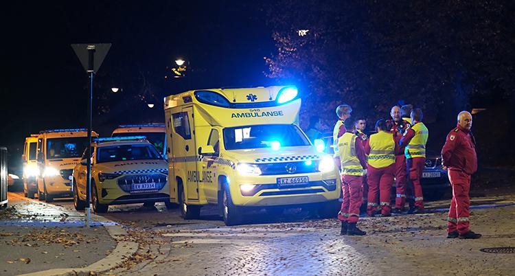 Bilden är tagen utomhus. Det är mörkt. Flera ambulanser står på rad. Personal står utanför.