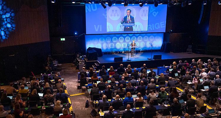 Massa människor sitter i en stor sal.