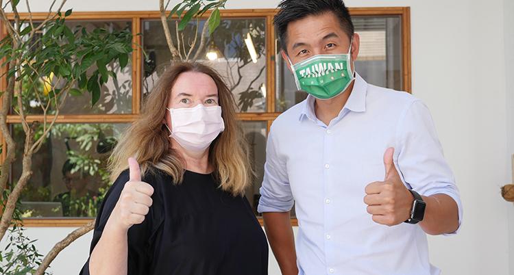 En man och en kvinna med munskydd gör tummen upp.