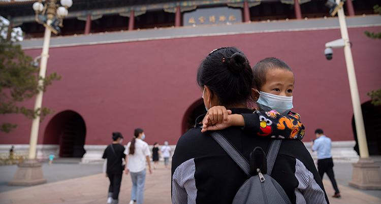 Ett barn med munskydd blir buren av en kvinna.