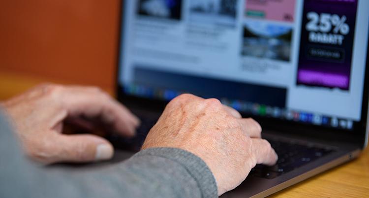 Händerna ligger mot tangenterna på en bärbar dator på ett bord