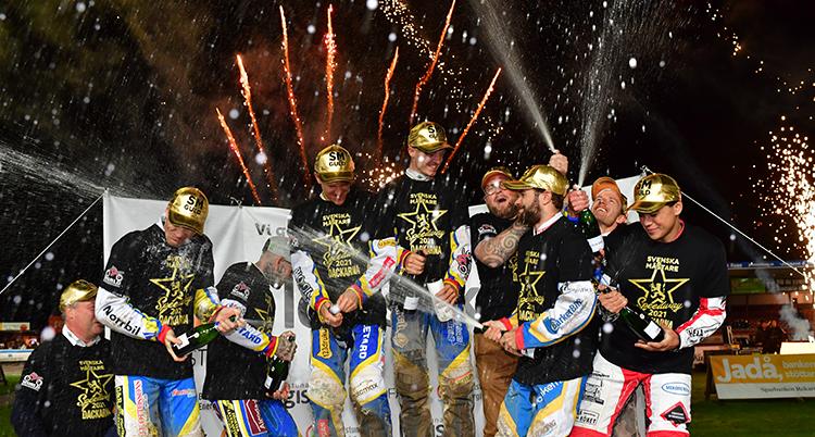 De står i en grupp på ett podium, de har guldhattar och öppnar champagne. Bakom syns fyrverkerier.