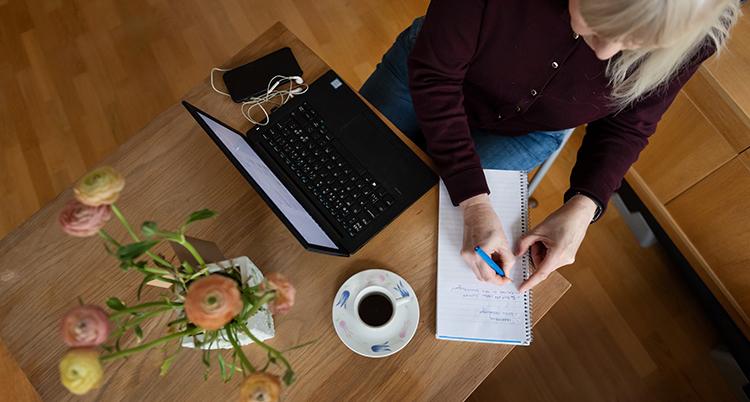Hon sitter vid ett bord med en dator, mobil, en blombukett och kaffe.
