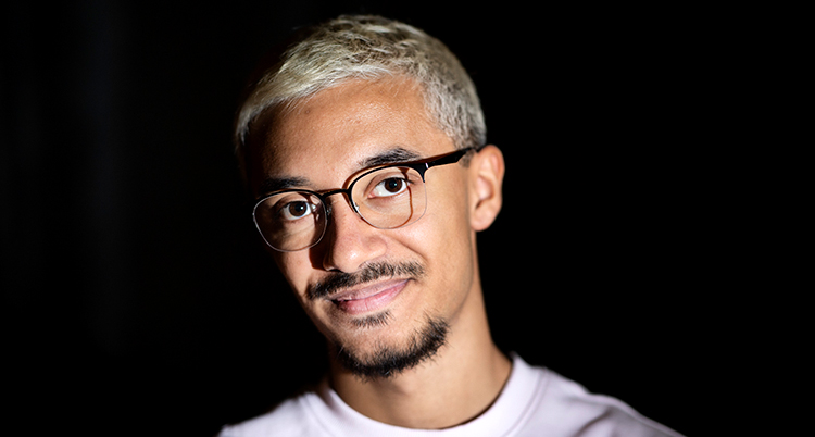 Han har blont hår,mörkt skägg och glasögon och tittar in i kameran.