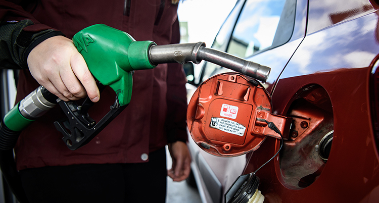 En hand håller i en bensinslang och ska tanka sin bil.