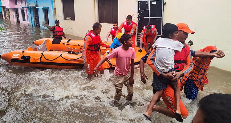 En orange båt syns på en väg som svämmat över. Flera personer vadar i vattnet.