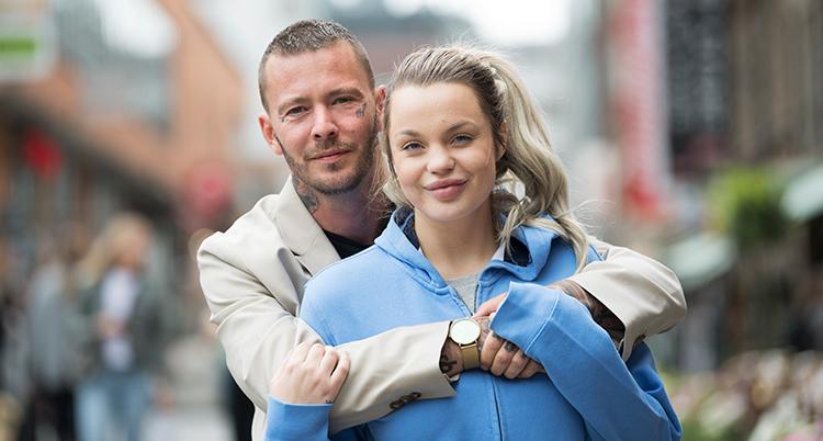 Han står bakom henne och håller armarna om henne. De står på en gata utomhus.