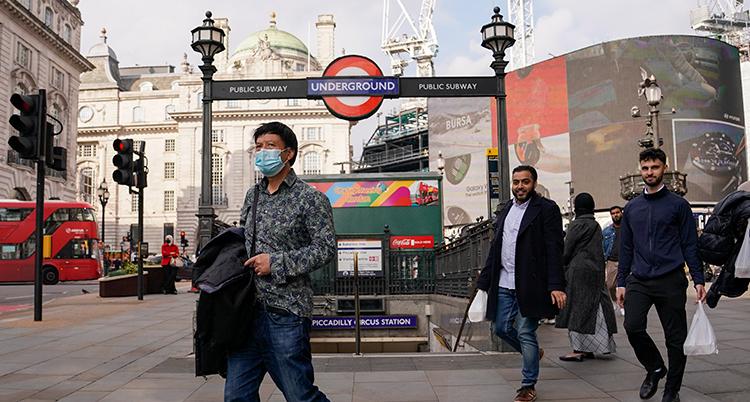 En man med munskydd går förbi en station till tunnelbanan i London.