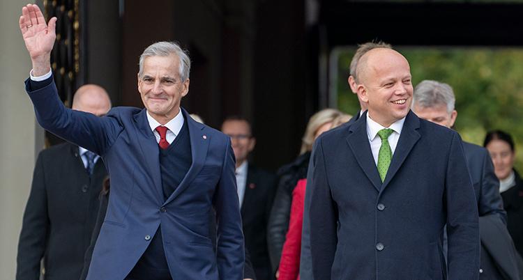 Två män som ler. En av dem vinkar