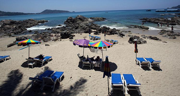 En sandstrand, hav och berg i horisonten. Blå solsängar och parasoll finns på stranden