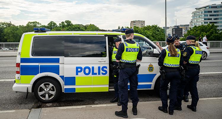 Poliser utanför en polisbil.