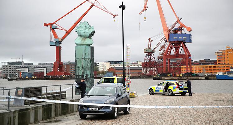 Stora lyftkranar syns i bakgrunden. Polistejp och polisbilar syns på piren.