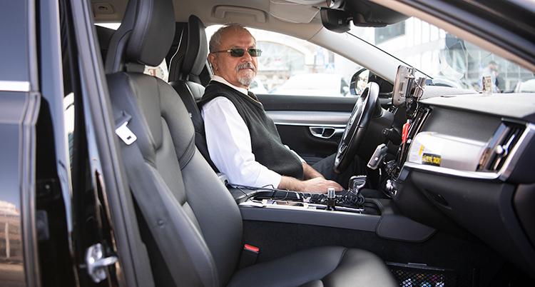 En chaufför sitter i framsätet på en taxi.