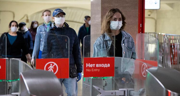 Flera personer går mot spärrarna. DE har jackor och munskydd.