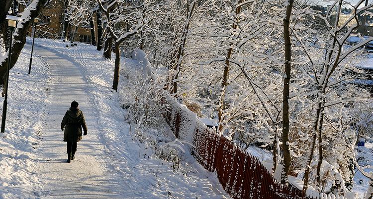 En person går på en väg som är täckt av snö.
